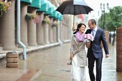 Hochzeitspaare, die zusammen an einem regnerischen Tag gehen Stockbild