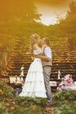 Hochzeitspaare in einer rustikalen Art, die nahe den Steinschritten umgeben durch die Heirat des Dekors am Herbstwald küsst Stockfotos