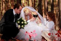 Hochzeitspaare, Mädchen und kleiner Hund im Freien Stockbild