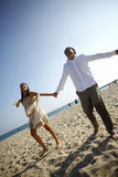 Hochzeitspaare mit den breiten Armen öffnen sich auf dem Strand Lizenzfreies Stockbild