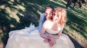 Hochzeitspaare sitzen auf dem Gras im Wald Lizenzfreies Stockbild