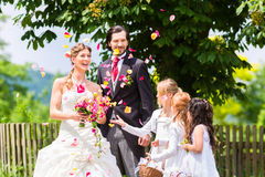 Hochzeitspaare und -brautjungfer, die Blumen duschen Lizenzfreies Stockfoto