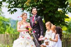 Hochzeitspaare und -brautjungfer, die Blumen duschen Stockfoto