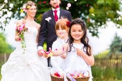 Hochzeitspaare und -brautjungfer, die Blumen duschen Stockbilder