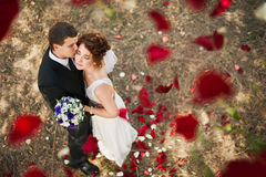 Hochzeitspaare unter einem Regen von rosafarbenen Blumenblättern Stockfotos