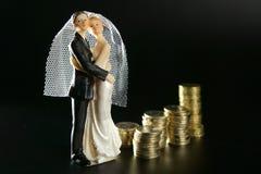 Hochzeitspaarfigürchen und goldene Münzen Lizenzfreies Stockfoto