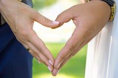 Hochzeitspaarhändchenhalten auf Naturhintergrund Stockfotos