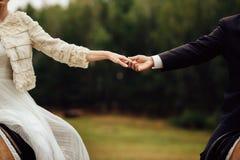 Hochzeitspaarhändchenhalten, das auf den Pferden sitzt Stockbild