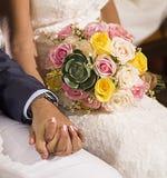 Hochzeitspaarhändchenhalten an der Zeremonie stockfotografie