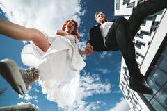 Hochzeitspaarspringen lizenzfreie stockbilder