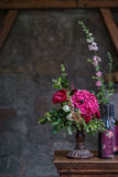 Hochzeitspfingstrosenblumenstrauß mit Weinflaschen gegen Weinlesedunklen Steinhintergrund Rustikale Art Stockbilder