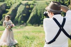 Hochzeitsphotograph macht Fotos der Braut und des Bräutigams in der Natur, Foto der schönen Kunst Stockbild