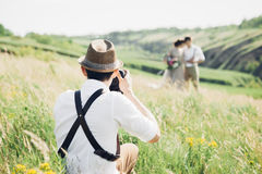 Hochzeitsphotograph macht Fotos der Braut und des Bräutigams in der Natur, Foto der schönen Kunst Stockbilder