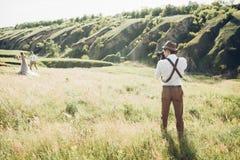 Hochzeitsphotograph macht Fotos der Braut und des Bräutigams in der Natur, Foto der schönen Kunst Stockfotos