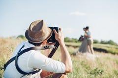 Hochzeitsphotograph macht Fotos der Braut und des Bräutigams in der Natur, Foto der schönen Kunst Lizenzfreie Stockfotografie
