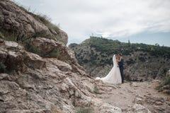 Hochzeitsphotographie eines jungen Paares, der Braut und des Bräutigams in einem Berggebiet im Sommer Stockfoto