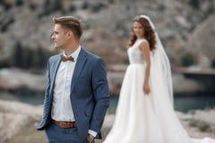 Hochzeitsphotographie eines jungen Paares, der Braut und des Bräutigams in einem Berggebiet im Sommer Stockfotografie