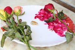Hochzeitsringe auf Blumen Stockbilder
