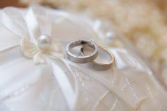 Hochzeitsringe auf dem Kissen Stockbilder
