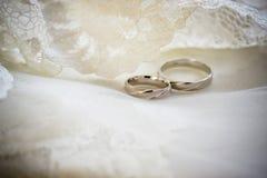 Hochzeitsringe auf einem Spitzehintergrund Lizenzfreie Stockbilder