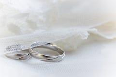 Hochzeitsringe auf einem Spitzehintergrund Lizenzfreie Stockfotografie