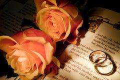 Hochzeitsringe auf einer Bibel mit dem Entstehungsgeschichtetext Lizenzfreies Stockbild