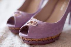Hochzeitsringe auf lila Velourslederschuhen Stockfoto