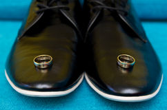 Hochzeitsringe auf Schuhen stockfoto