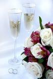 Hochzeitsringe, Champagner und Blumen Stockbilder