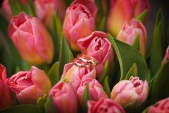 Hochzeitsringe in den Blumen Stockfoto