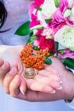 Hochzeitsringe in den Händen Stockfotos