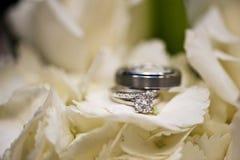 Hochzeitsringe in den weißen Blumen Stockfoto