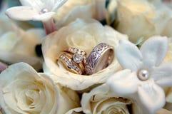 Hochzeitsringe in den weißen Blumen Lizenzfreies Stockfoto