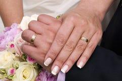 Hochzeitsringe, -hände und -blumenstrauß der Rosen. Lizenzfreie Stockbilder