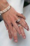 Hochzeitsringe, Holdinghände Stockbild