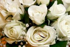 Hochzeitsringe im rosafarbenen Blumenstrauß Stockbild
