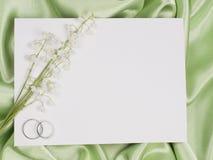 Hochzeitsringe, -karte und -lilie des Tales Stockfoto