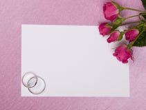 Hochzeitsringe, -karte und -rosen Stockfotografie