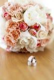 Hochzeitsringe mit Blumenstrauß Lizenzfreies Stockfoto