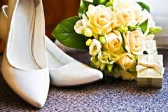 Hochzeitsringe mit Blumenstrauß- und Absatzschuhen Stockfotografie