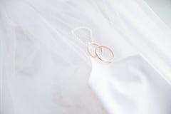 Hochzeitsringe mit Handschuh auf Schleier Stockbilder