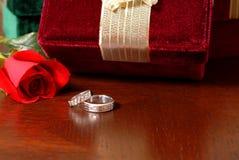 Hochzeitsringe mit Weihnachtsgeschenken und einer Rose Lizenzfreies Stockbild