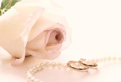 Hochzeitsringe, Perlenkorne und stiegen Lizenzfreies Stockbild