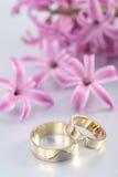Hochzeitsringe u. purpurrote Blüte stockbilder
