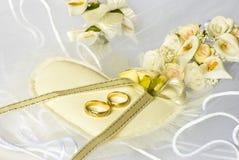 Hochzeitsringe und -blumen über Schleier stockbild