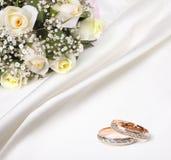 Hochzeitsringe und -blumenstrauß Stockfotografie