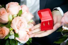 Hochzeitsringe und -blumenstrauß Stockbild