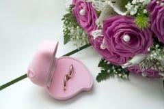 Hochzeitsringe und Blumenstrauß der Braut Stockfotografie
