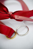 Hochzeitsringe und ein rotes Farbband Lizenzfreies Stockfoto