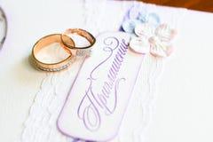 Hochzeitsringe und eine Einladung Stockfotos